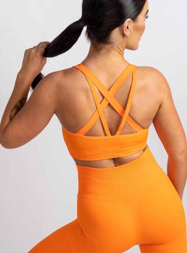 woman wearing organe crop top and matching leggings